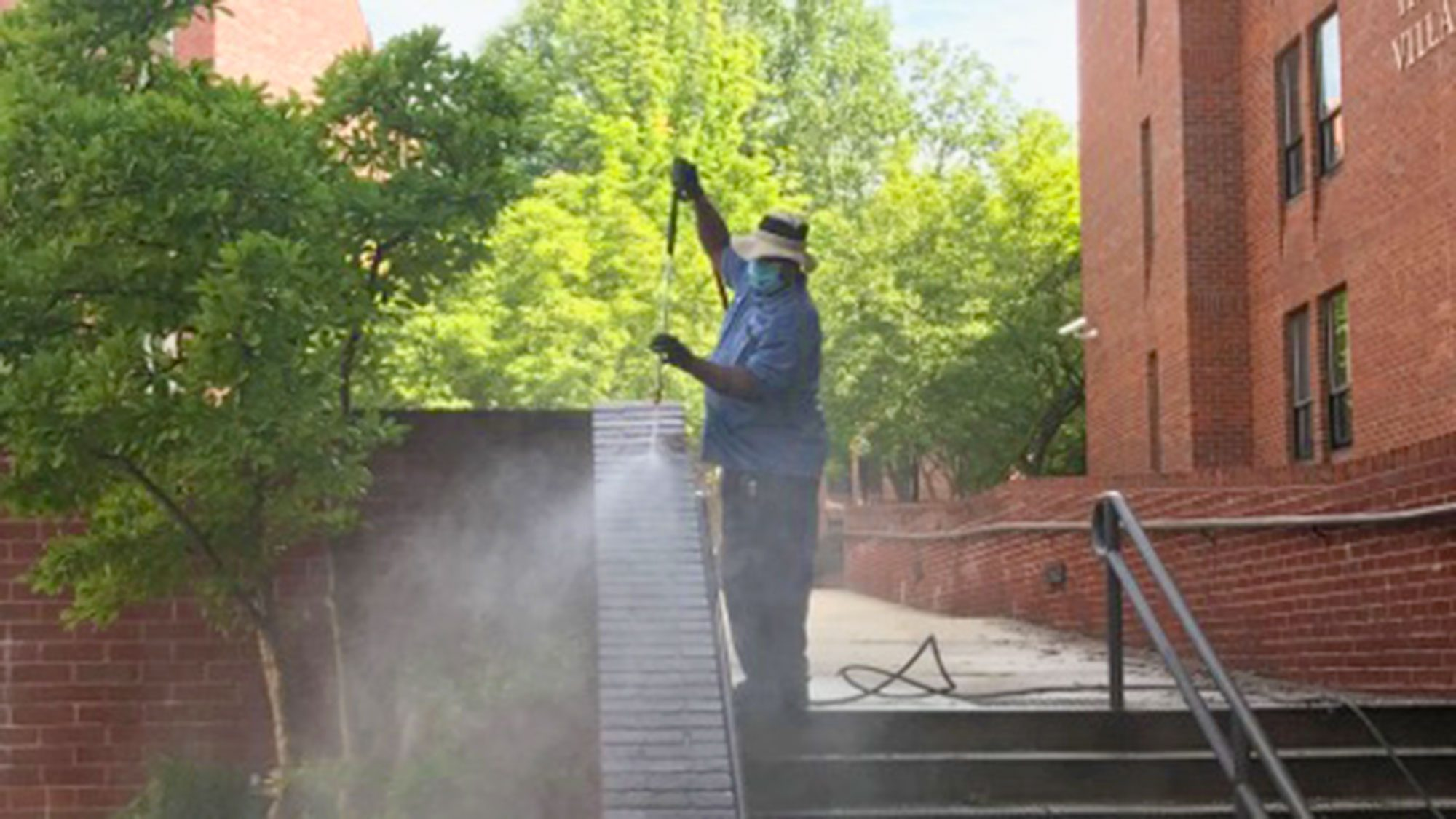 A man wears a mask while pressure washing the brick around stairs on campus.