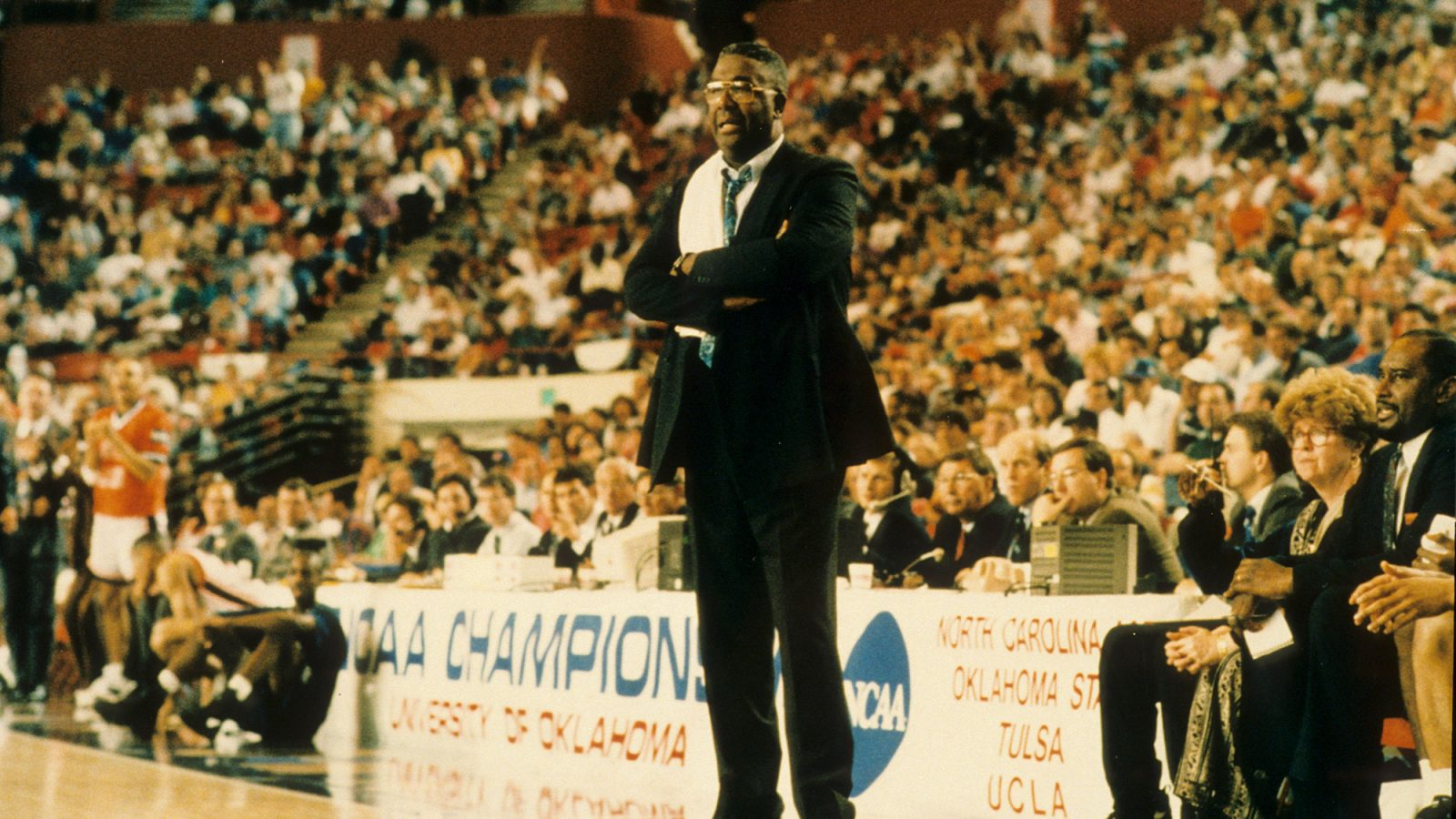 John Thompson Jr. stands courtside with his arms folded and a towel hanging from his shoulder.