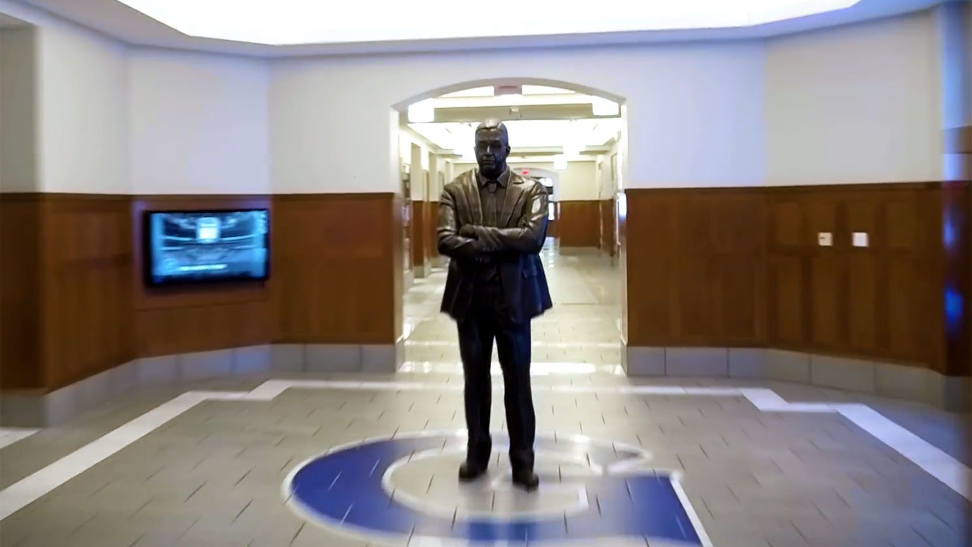 A bronze statue of john Thompson Jr. stands in the middle of the Georgetown Athletics logo inside the Thompson Athletic Center.