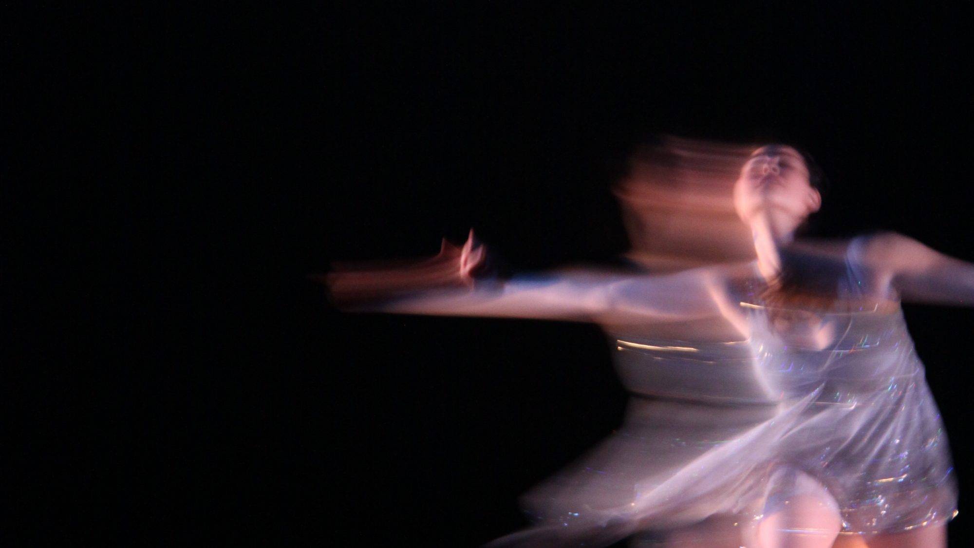 solo dancer from the GU Dance Company wears a silver sparkly leotard and spins against a black background