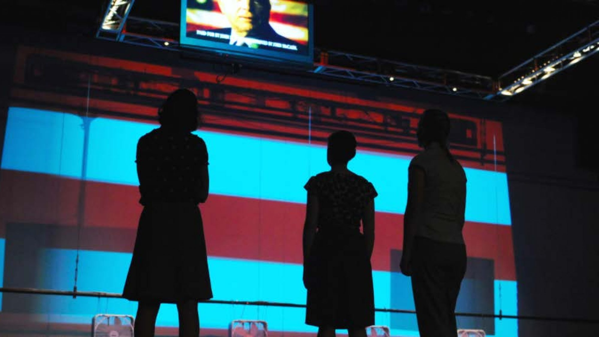 Student cast members in silhouette look up at a TV screen showing a political figure speaking in front of an American flag.