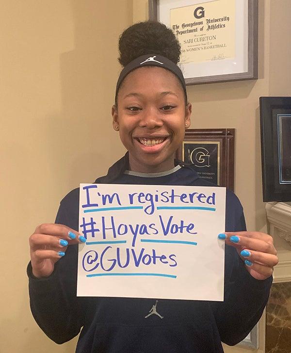 """Sari Cureton holds up a sign reading """"I'm registered #HoyasVote @GUVotes"""