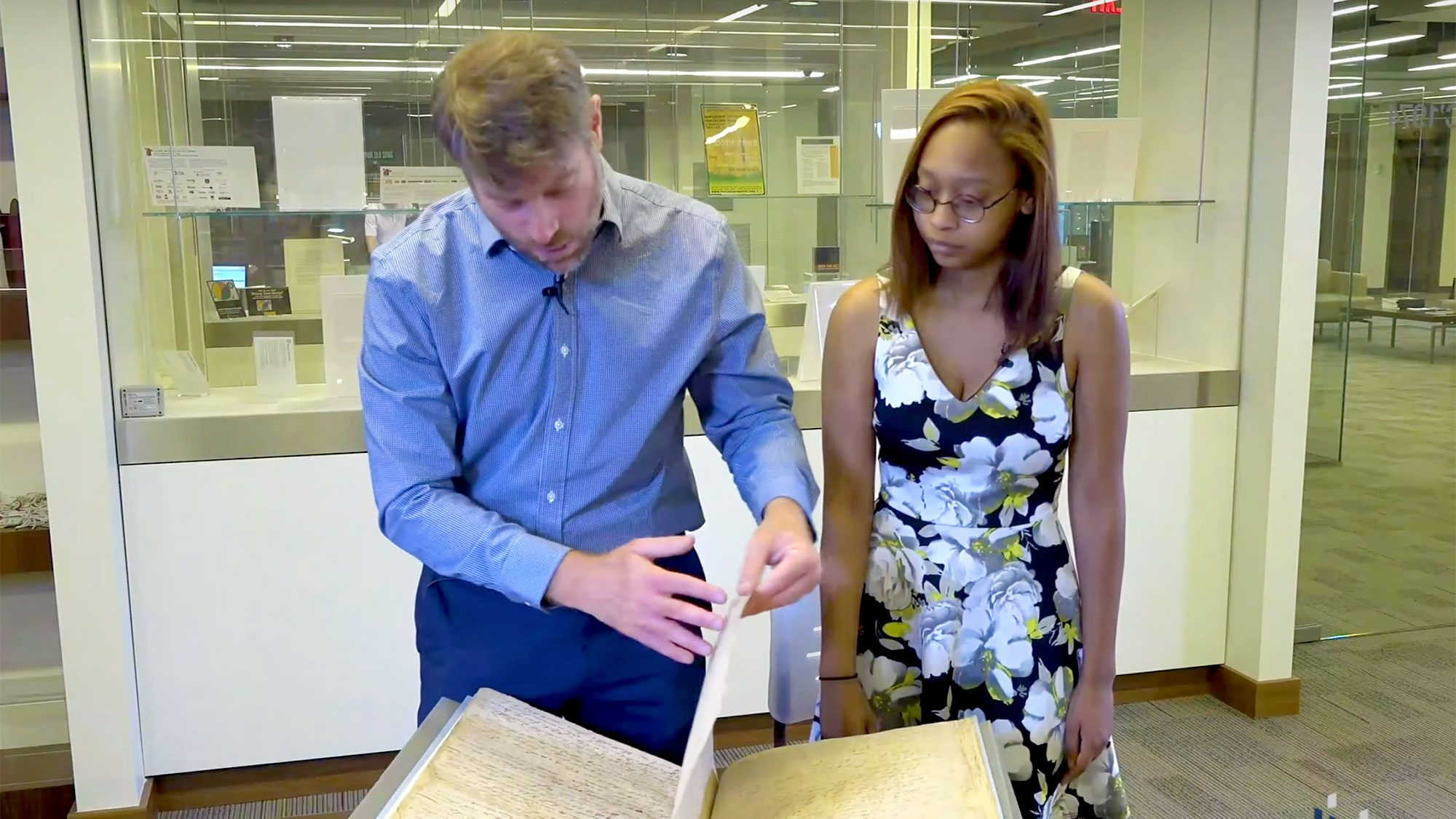 Adam Rothman and a student look through a rare logbook in the library archives.