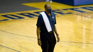 Patrick Ewing stands on court with a mask on his facew and towel draped over his shoulder.