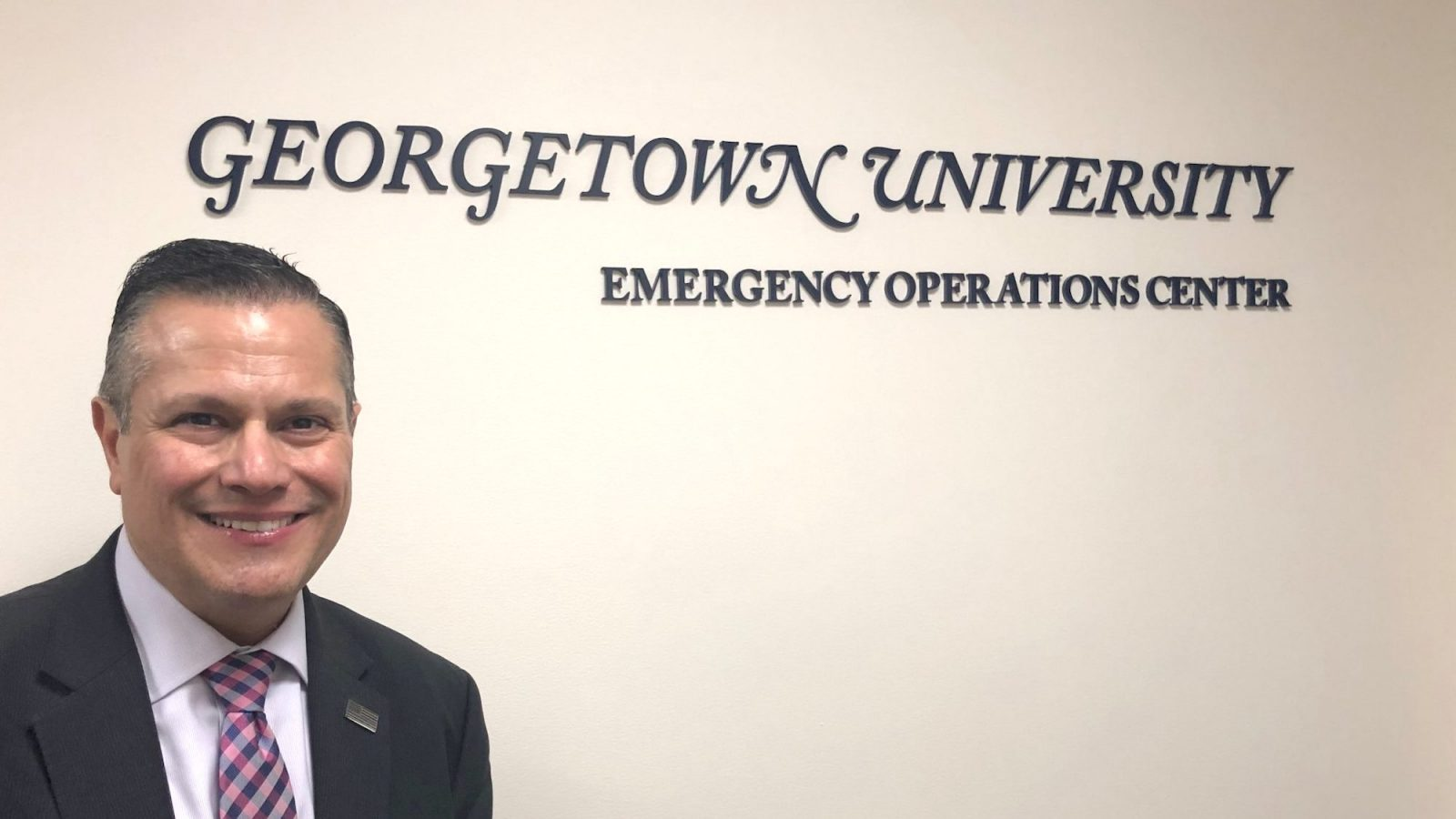 Marc Barbiere stands in front of Georgetown University Emergency Operations Center sign