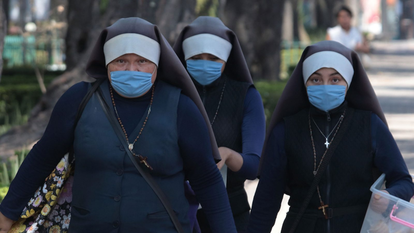 A group of nuns walk while wearing masks.