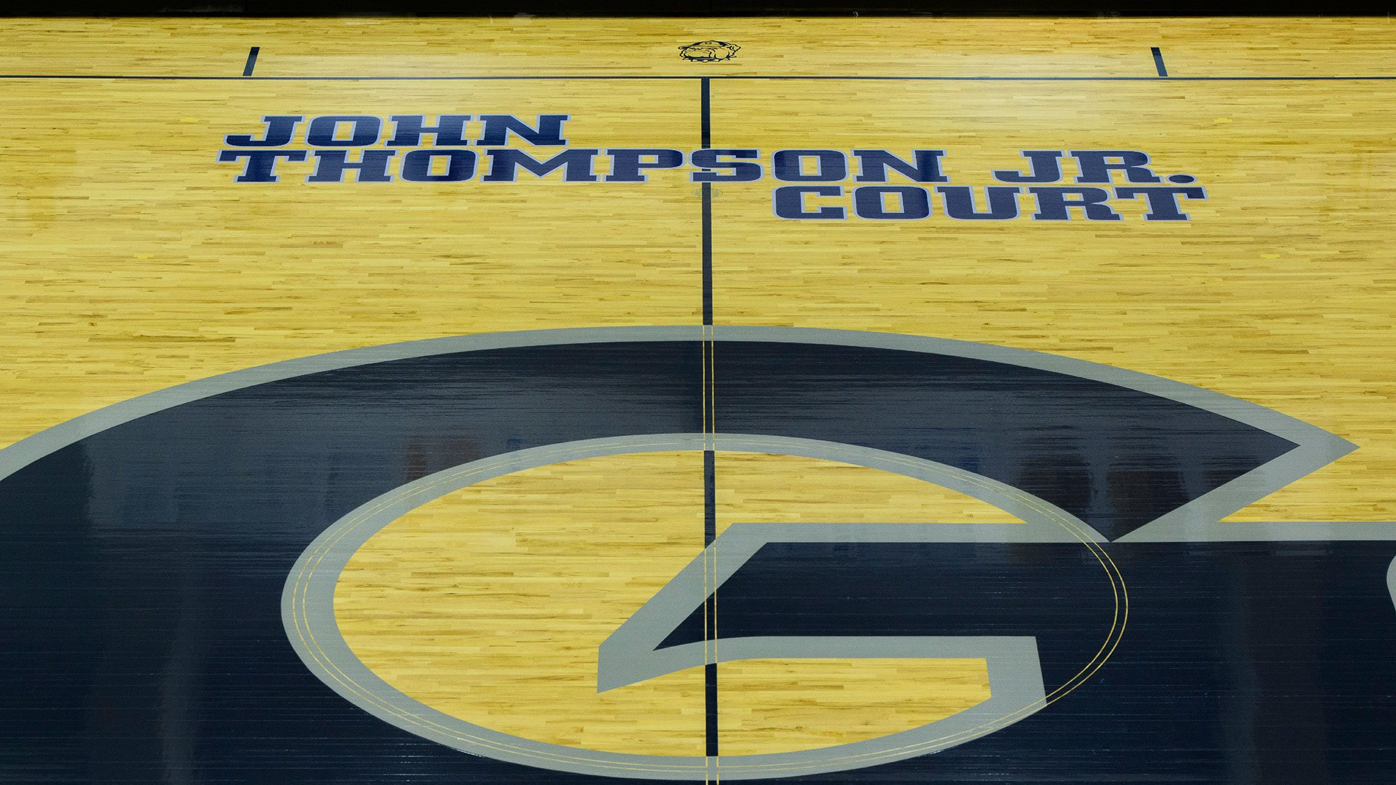 A basketball court with the Geogetown logo and John Thompson Jr. name on the court.
