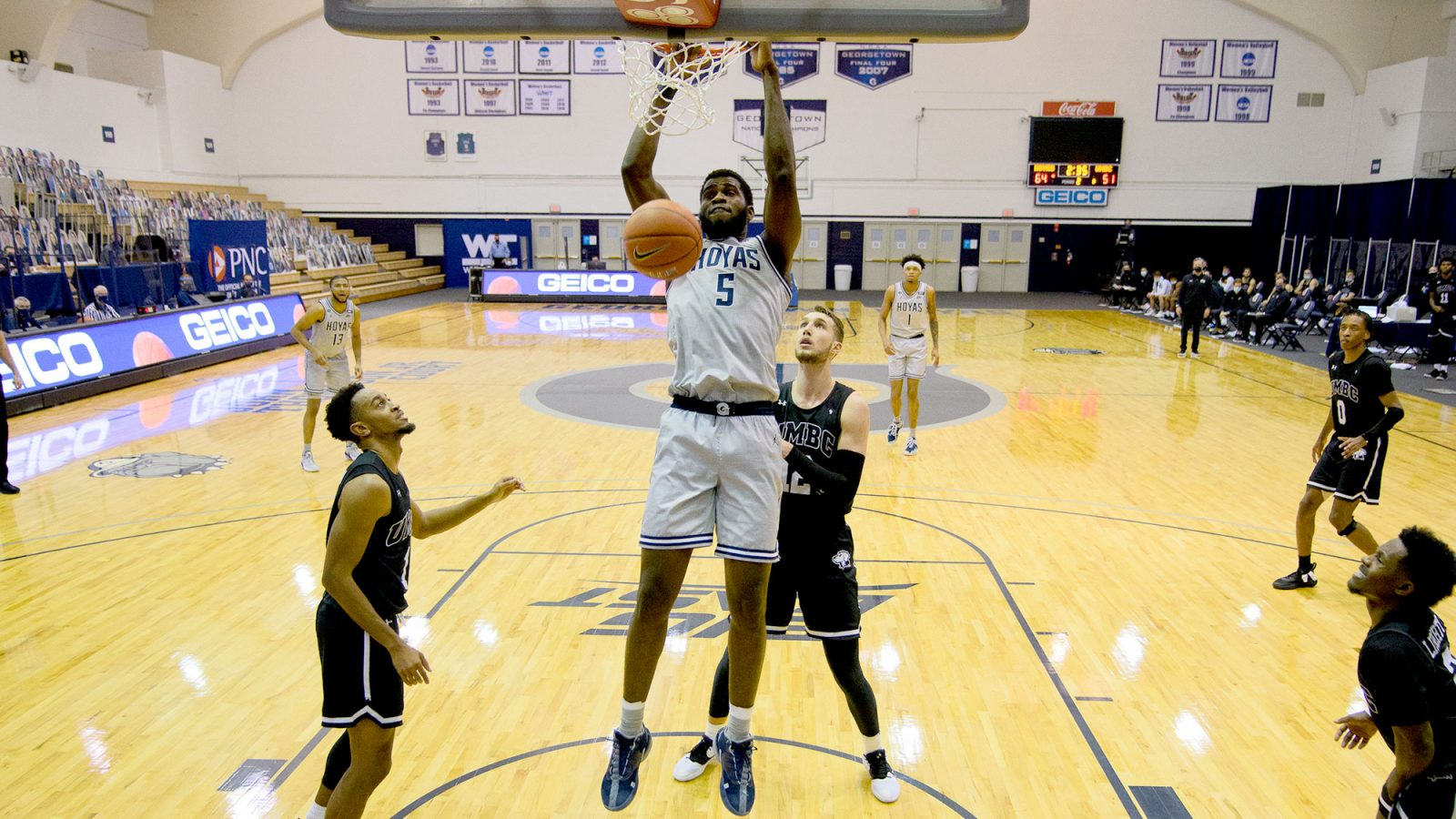 A Hoya basketball player dunks the ball in a basket as playerss from another team look on.