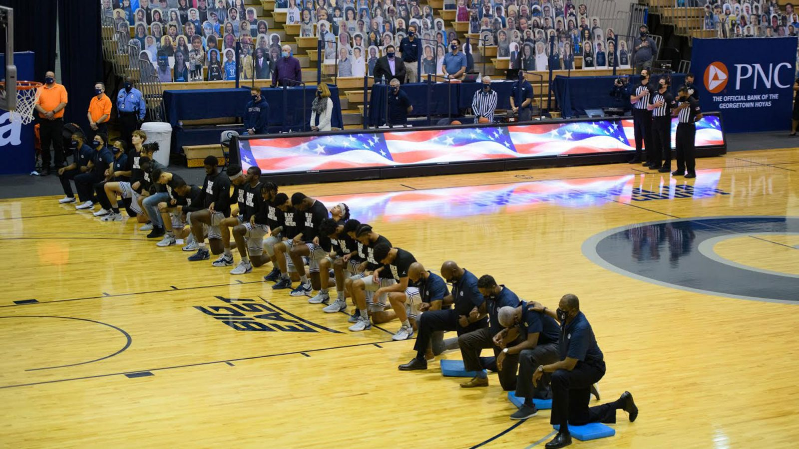 Basketball players kneel on the court before their game.