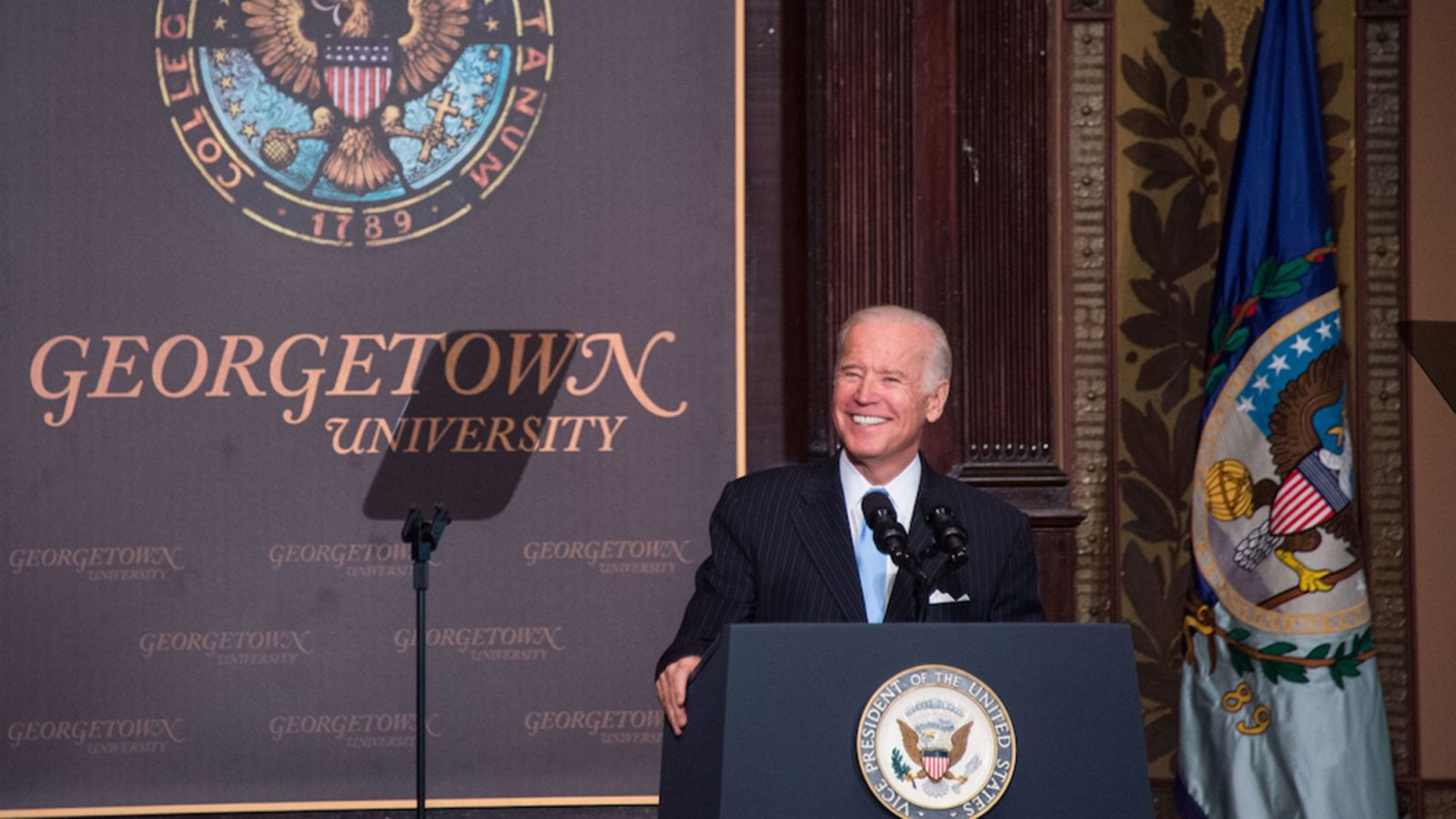 Joe Biden stands on the stage in Gaston Hall behind a lectern with a Georgetown University placard in the background.