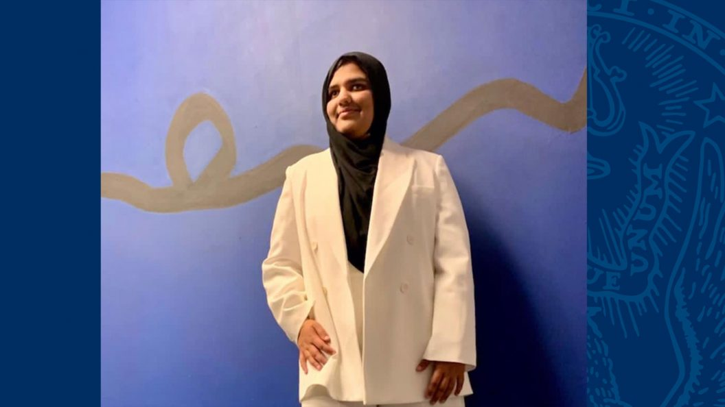 Khansa Maria stands against a wall wearing a white suit and black hijab.
