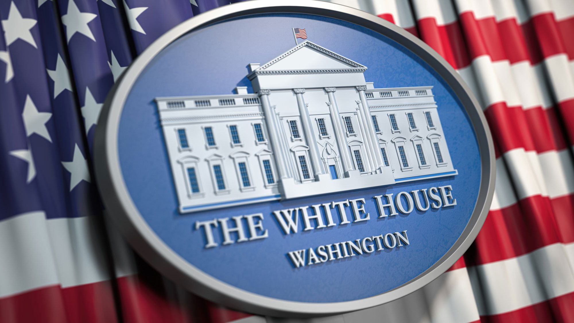 Oval White House plaque lies against an American flag backdrop.