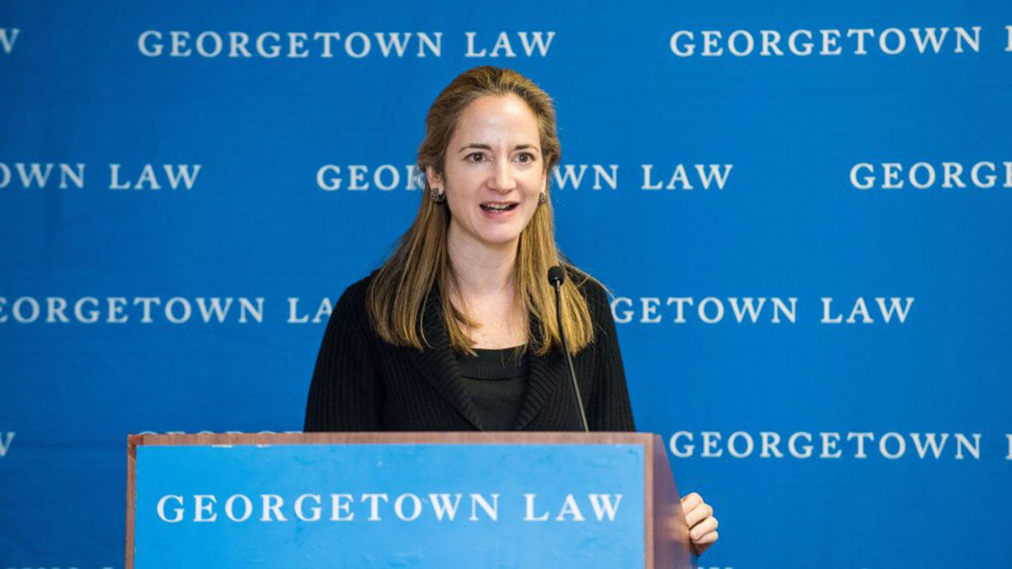 Avril Haines stands at a lectern with a microphone speaking in front of a blue Georgetown Law background.