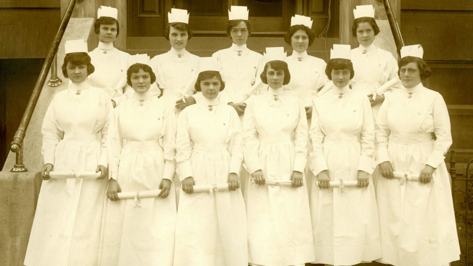 Eleven nurses stand in two rows on steps dressed on uniform in a 1920 photo.