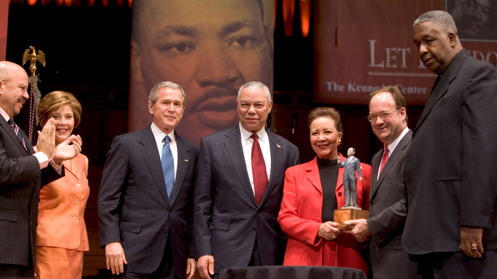 Tom Joyner, Laura Bush, George W. Bush and Colin Powell stand to the left of Alma Powell who is receiving an award from John J. DeGioia standing to her right with John Thompson Jr.
