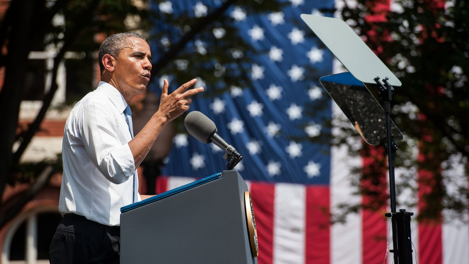 A side view of Barack Obama as he stands at a lectern delivering an address outside.