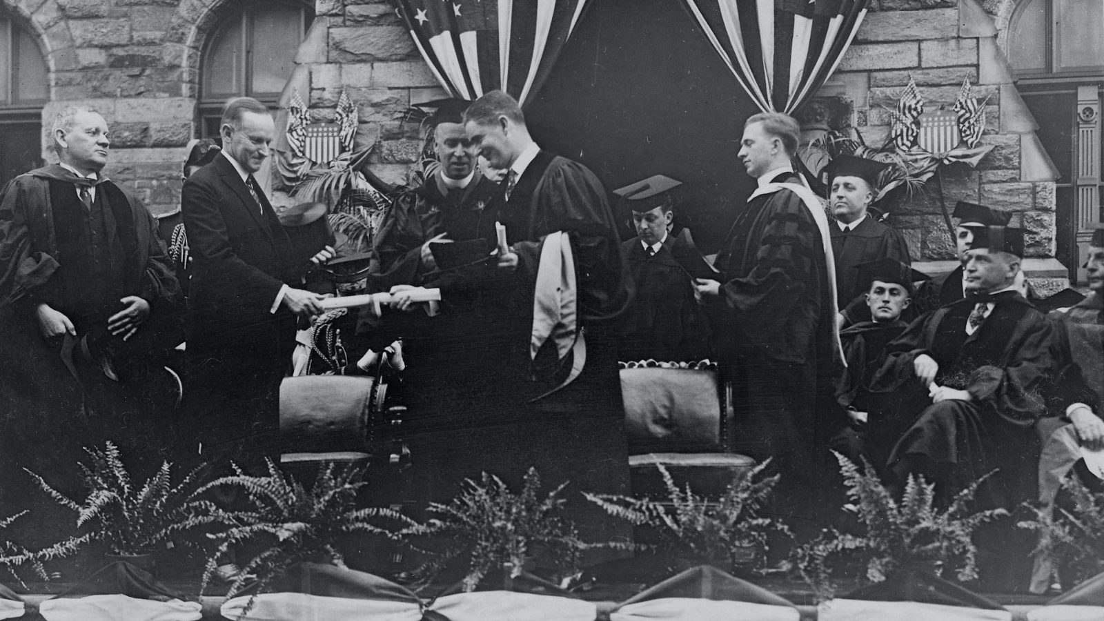 A black and white photo of President Calvin Coolidge participating in a Georgetown Commencement ceremony surrounded by individuals