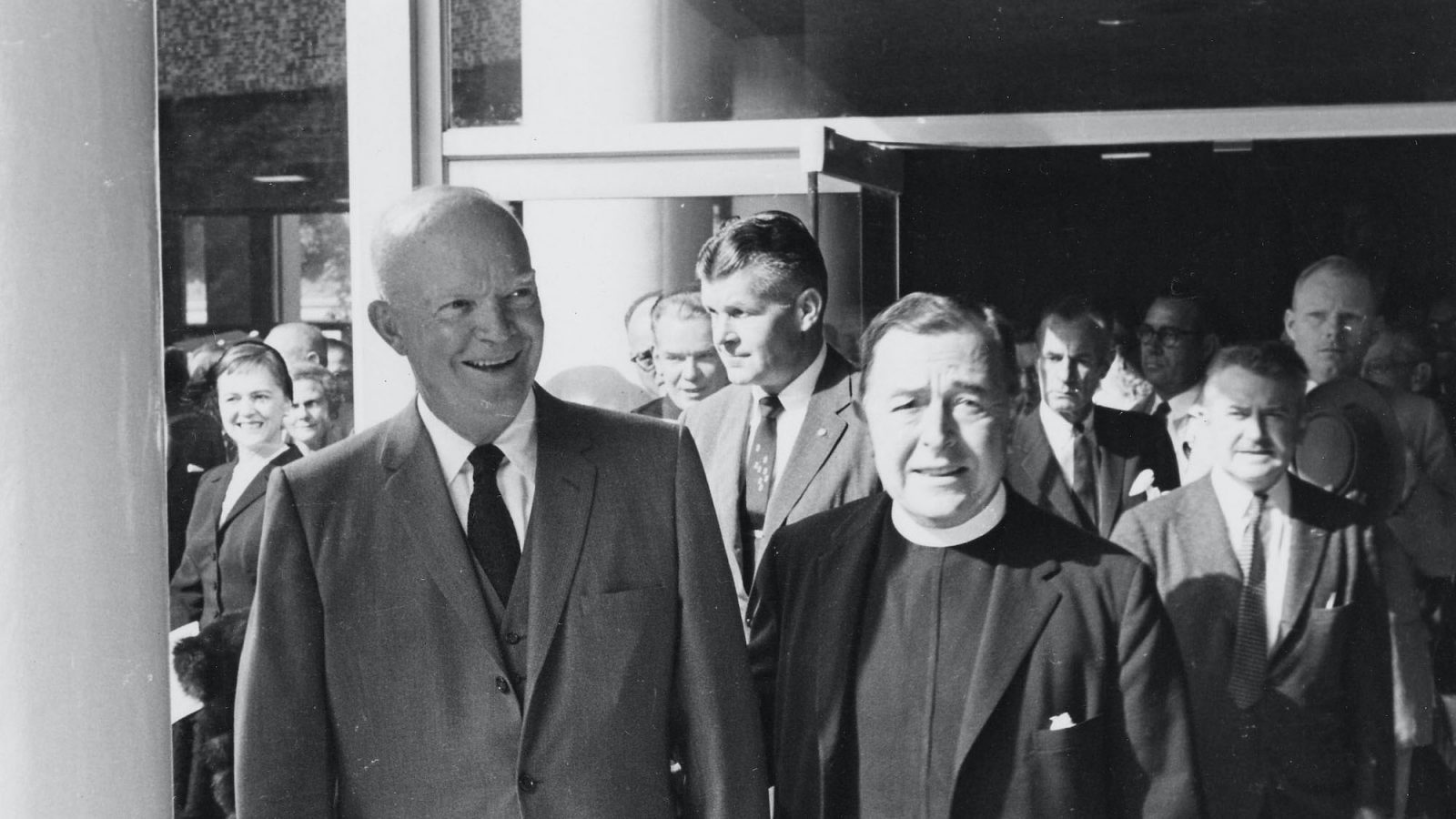 A black and white photograph of President Dwight Eisenhower exiting the Walsh Building with Father Edward B. Bunn