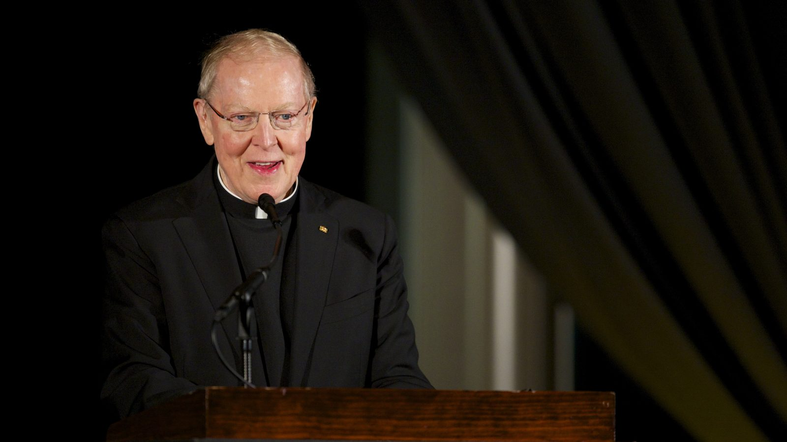Father Leo J. O'Donovan speaks at a podiium