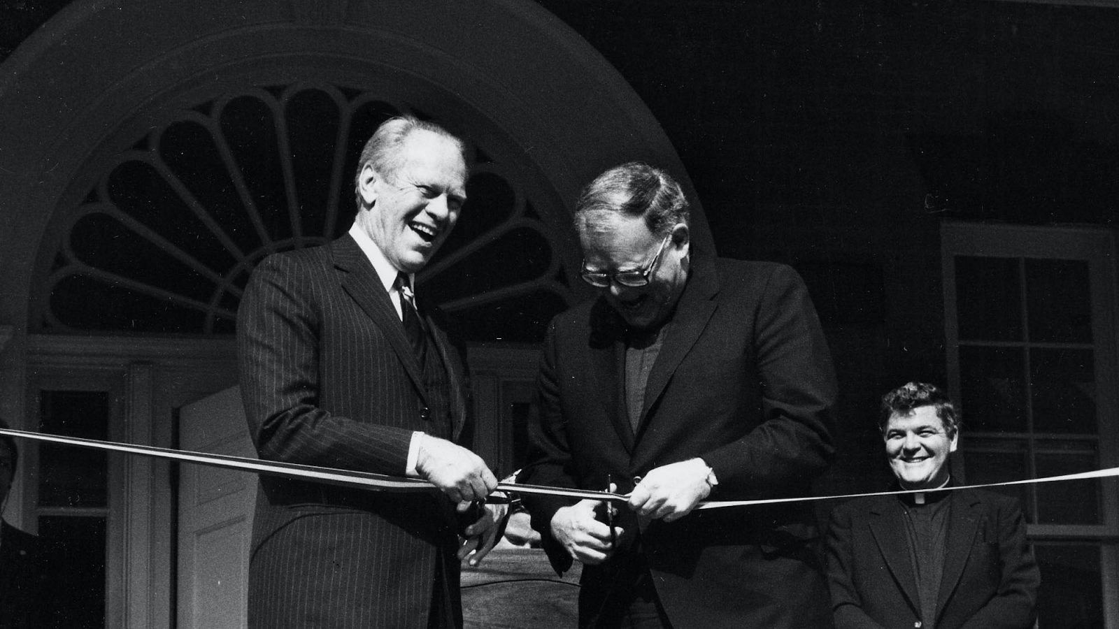 A black and white photo of President Gerald Ford on the steps of the Old North Building with Father Timothy Healy