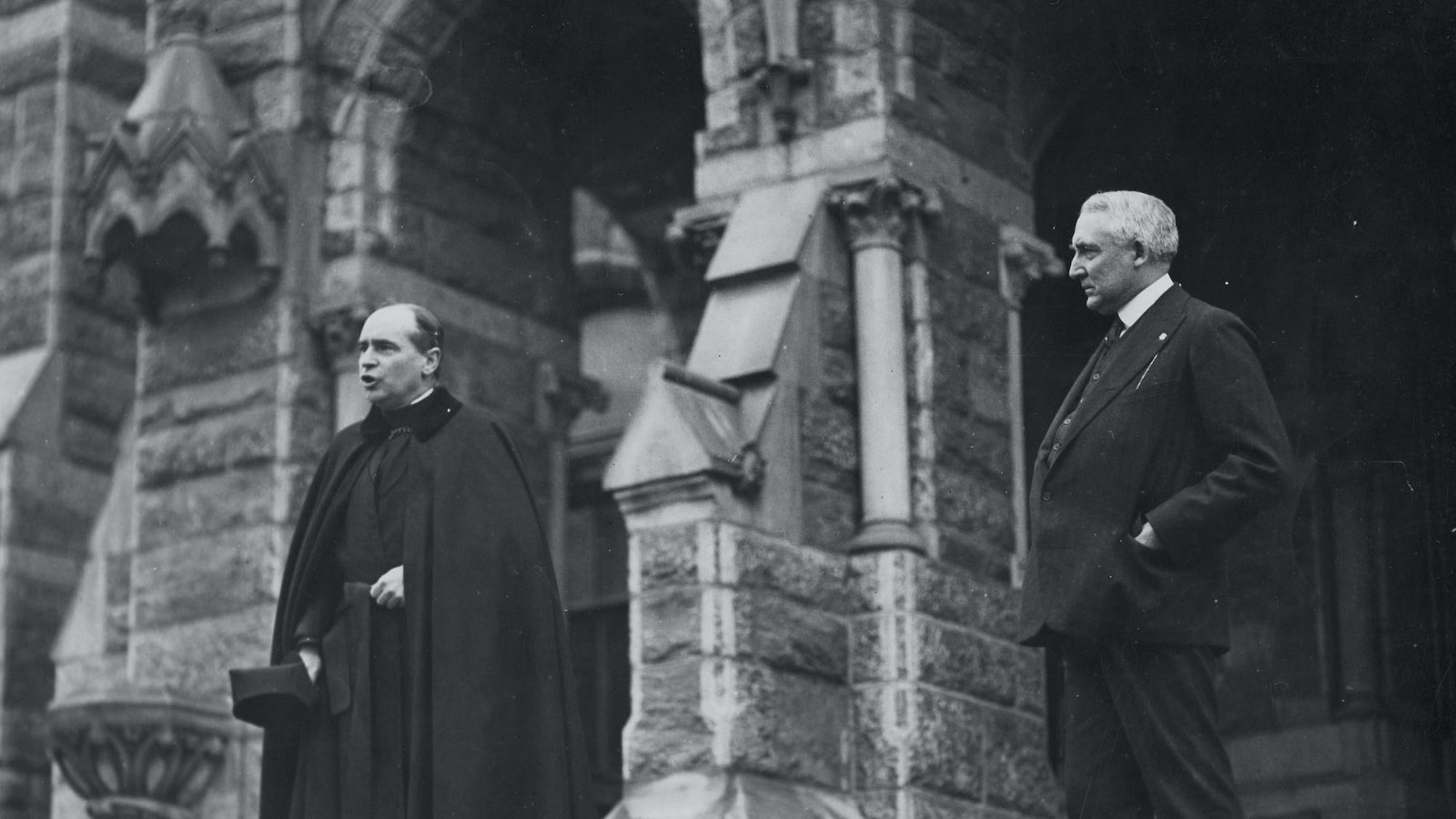 A black and white photo of President Warren Harding with a Jesuit priest on the step of Healy Hall