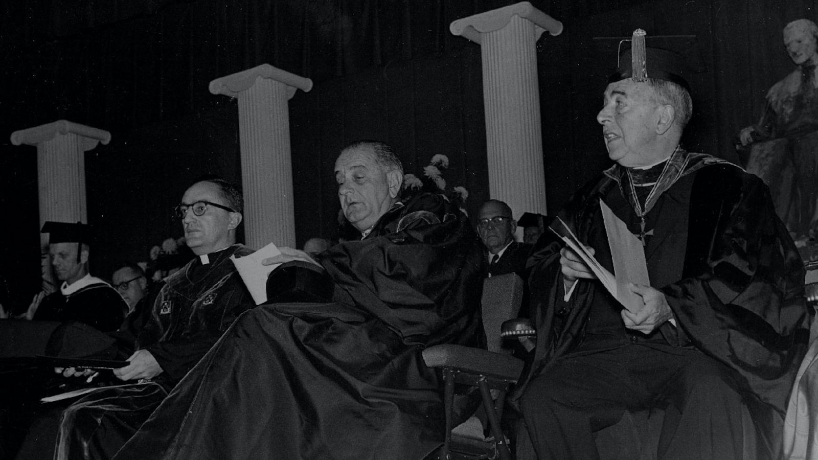 A black and white photo of President Lyndon Johnson at a Georgetown ceremony with faculty in academic robes