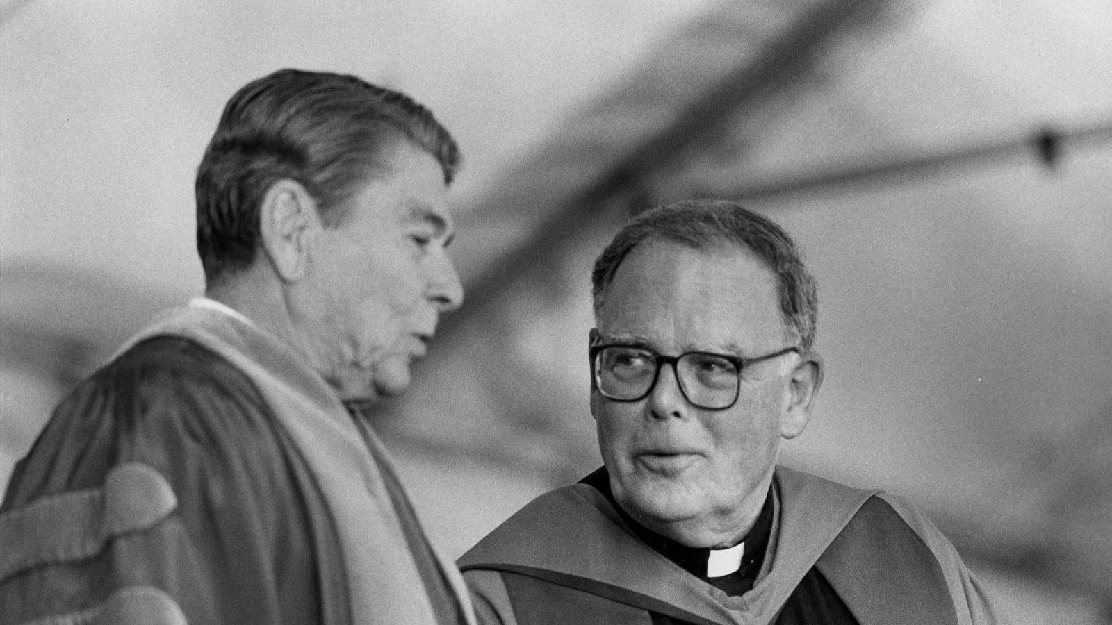 A black and white photo shows of President Ronald Reagan talking to Father Timothy Healy.