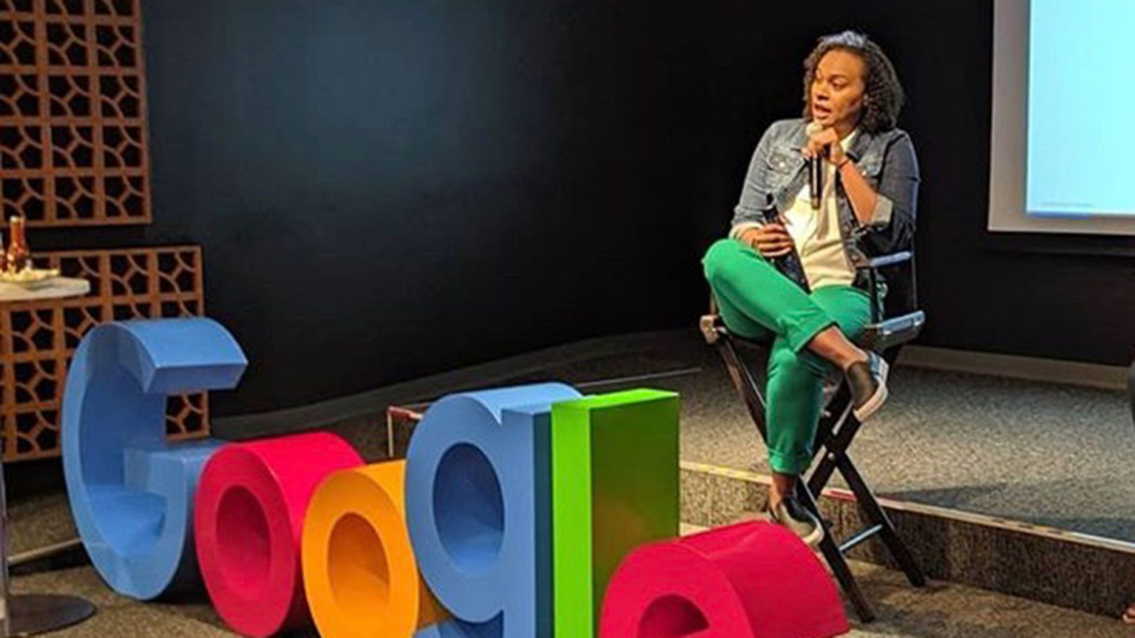 Cherizza Lundy sits in a chair on stage with a microphone in her hand and the Google logo in front of her.