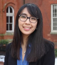 Sonya Hu in an outdoor photo standing in Dahlgren Quadrangle in front of Healy Hall and Maguire Hall