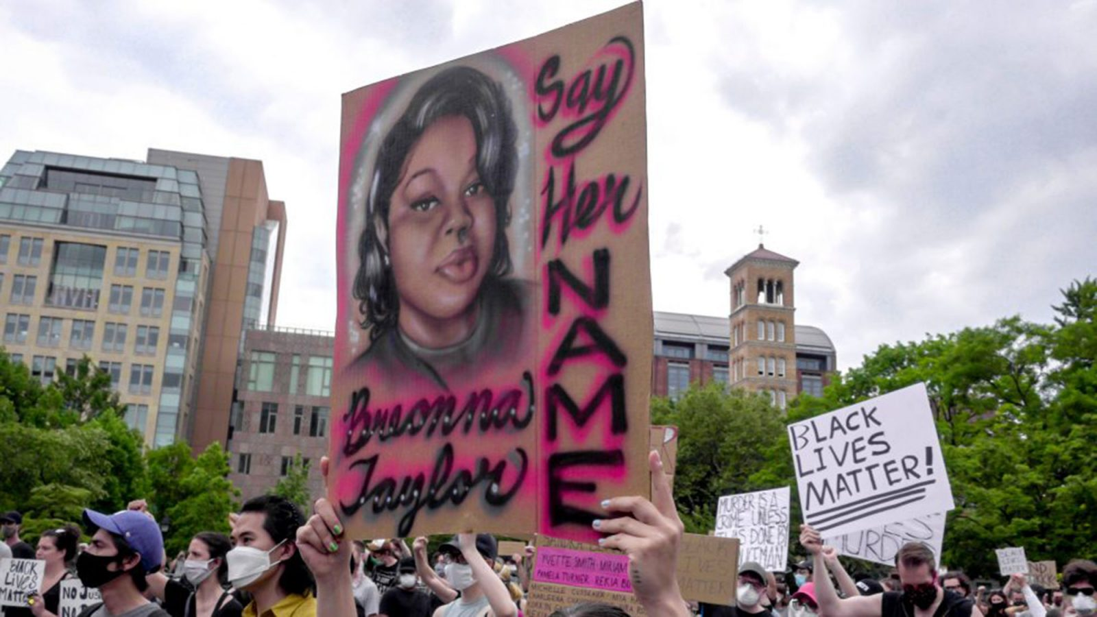 People stand in front of a mural of Breonna Taylor.