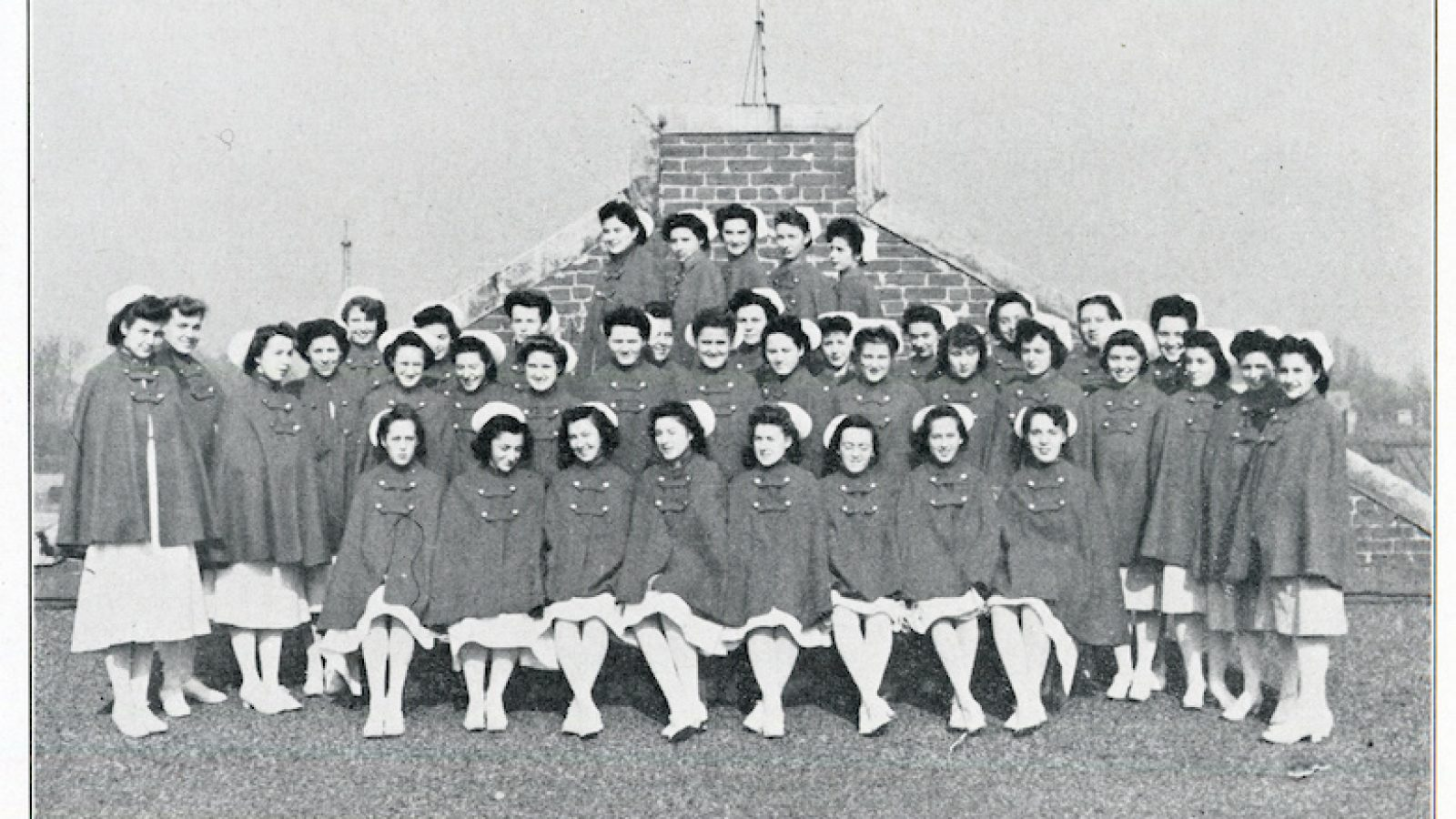 A historic photograph of the Georgetown nursing students in the Cadet Nurse Corps posing together outdoors in nursing uniforms