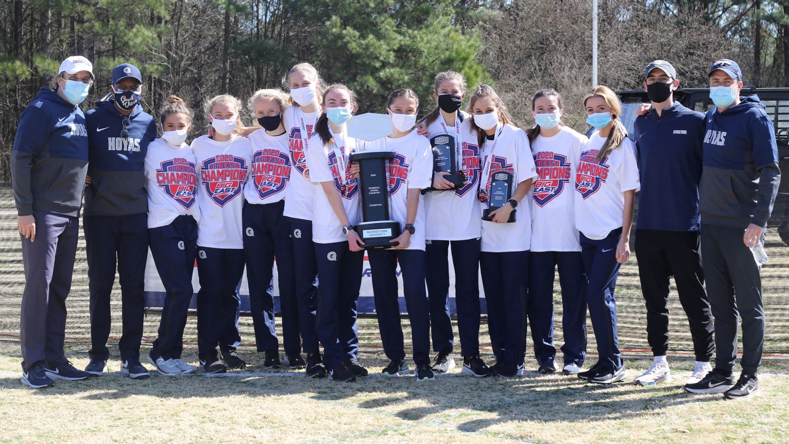 The women's cross country team and coaches pose with the BIG EAST Championship trophy.