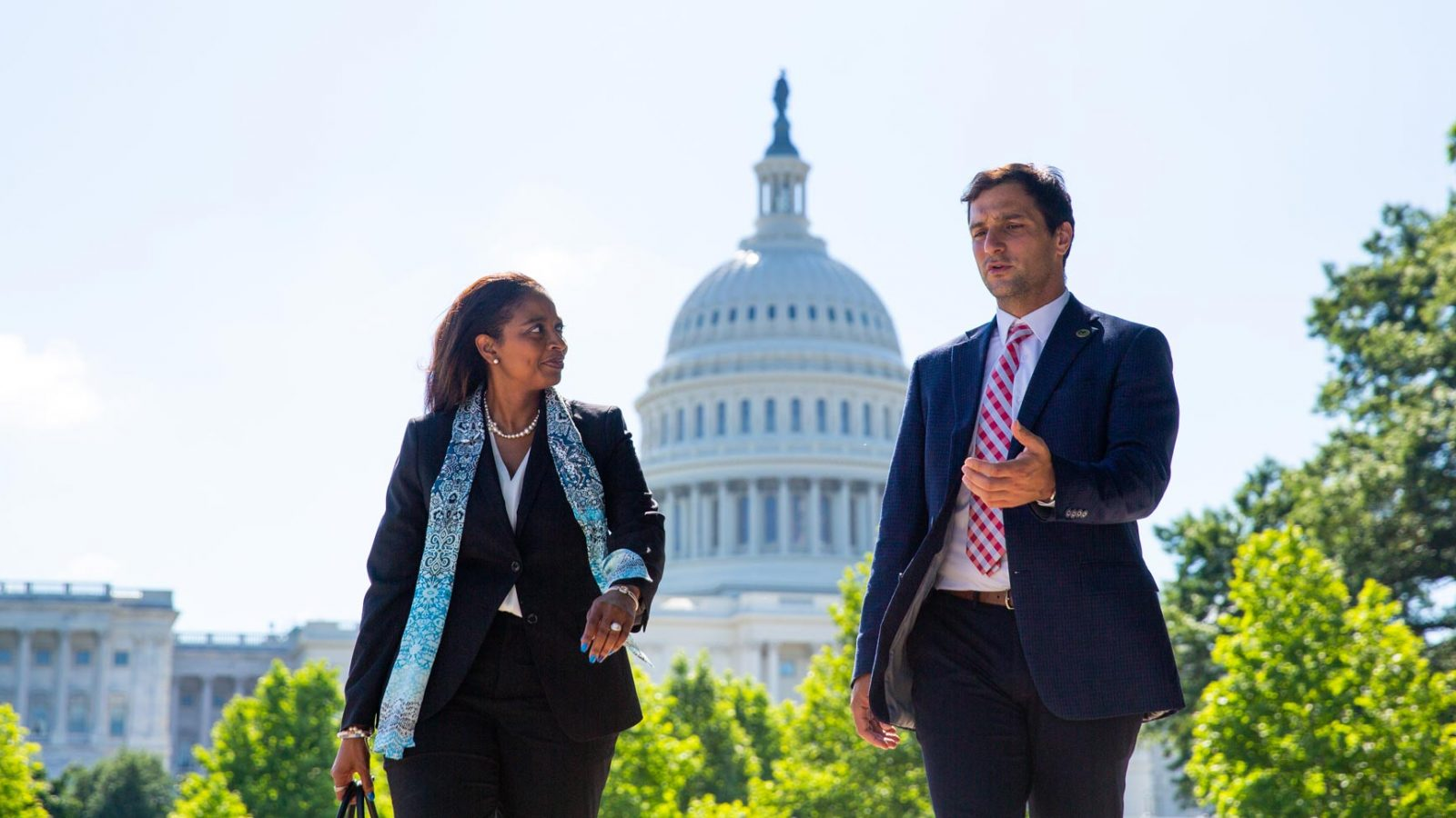 Woman and man in business clothes walk in front of the Capitol Building