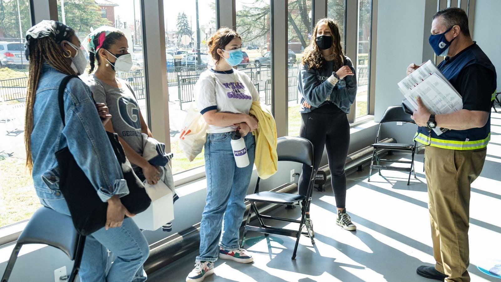 Marc Barbierie talks to student volunteers dressed in masks.