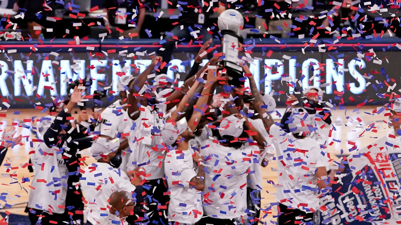The men's basketball team celebrate on the court after winning the BIG EAST championship as confetti falls.