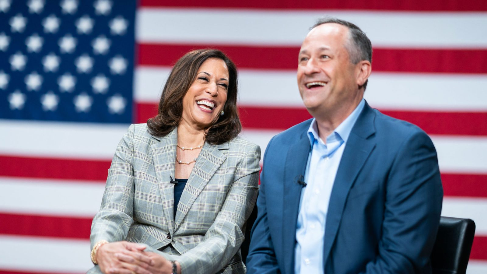 Kamala Harris and Douglas Emhoff share a laugh with the American flag in the background.