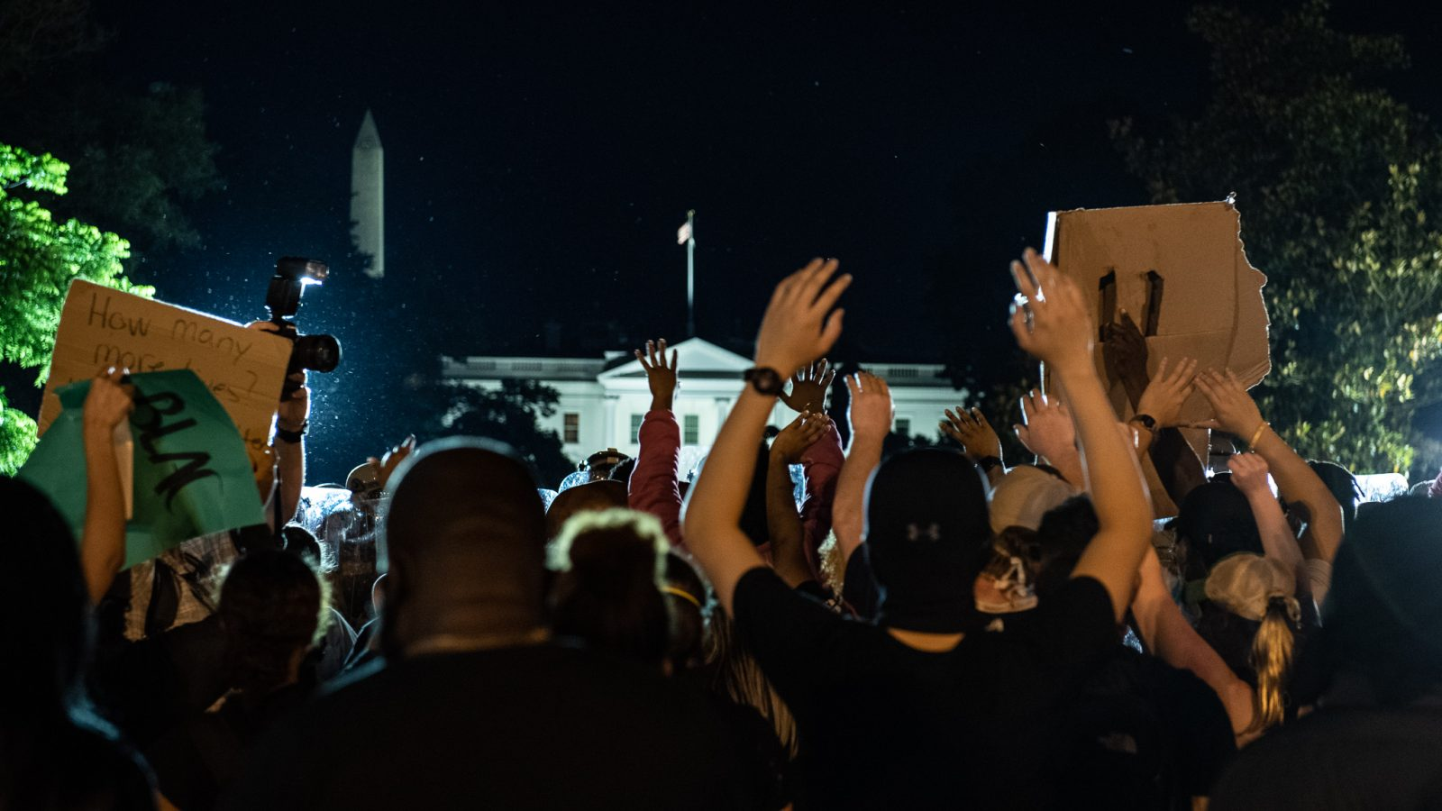 Racial justice protesters stand with their hands raised, with the White House in the background