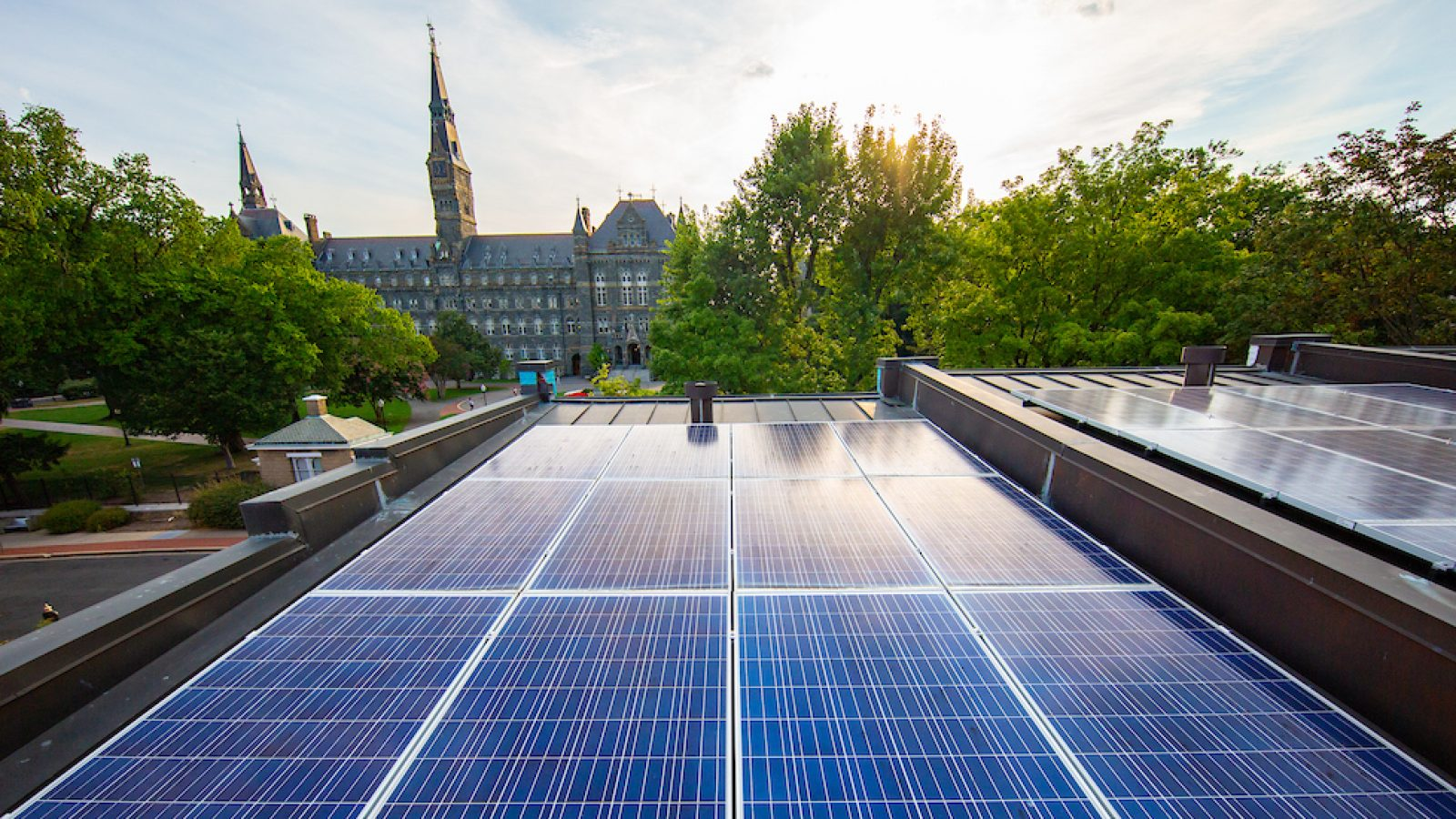 Solar panels on Georgetown townhouse rooftops with Healy Hall in the background