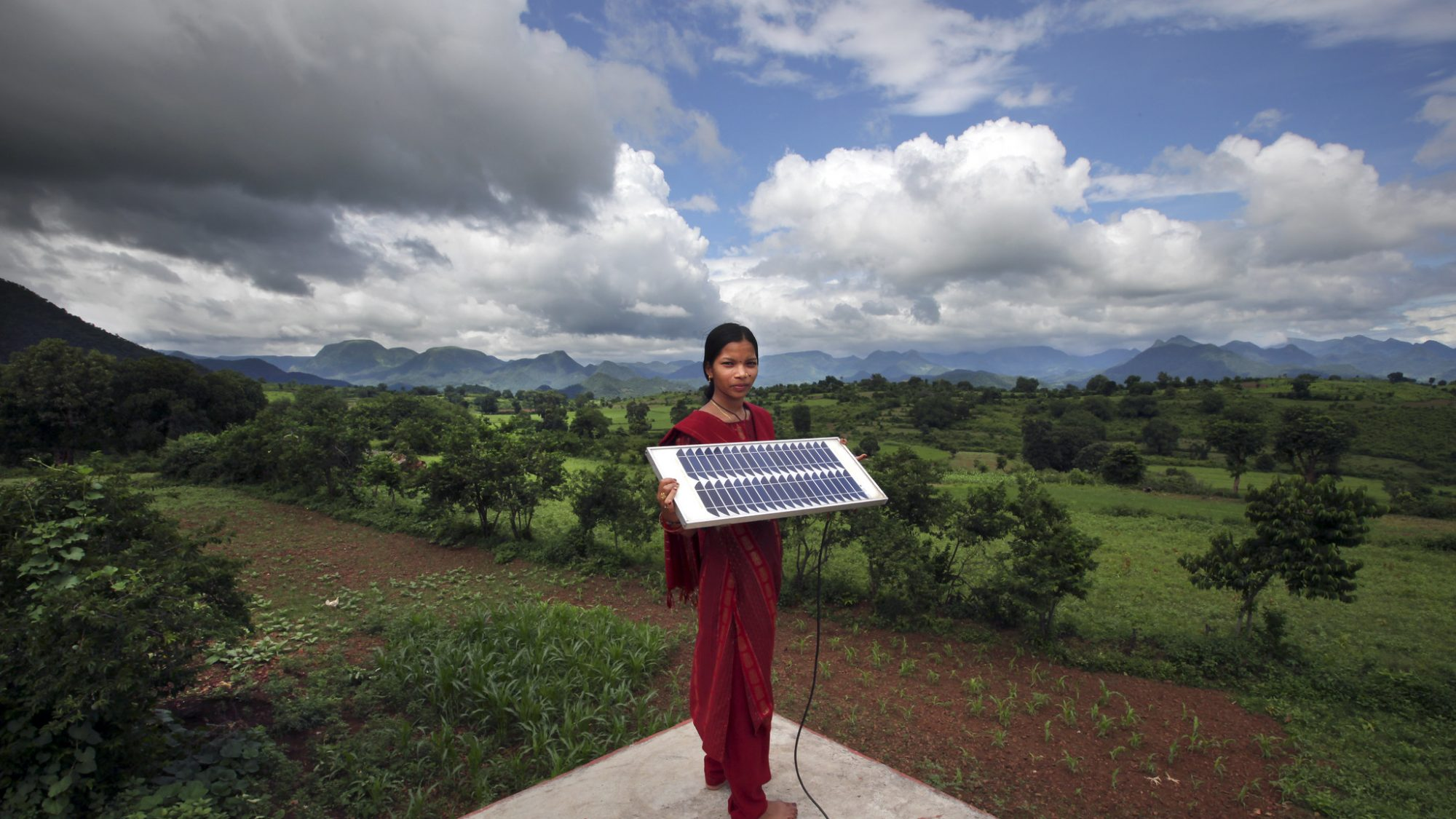 Girl holds solar panel in front of farm land
