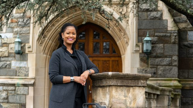 Soyica Diggs Colbert stands in front of a stone building