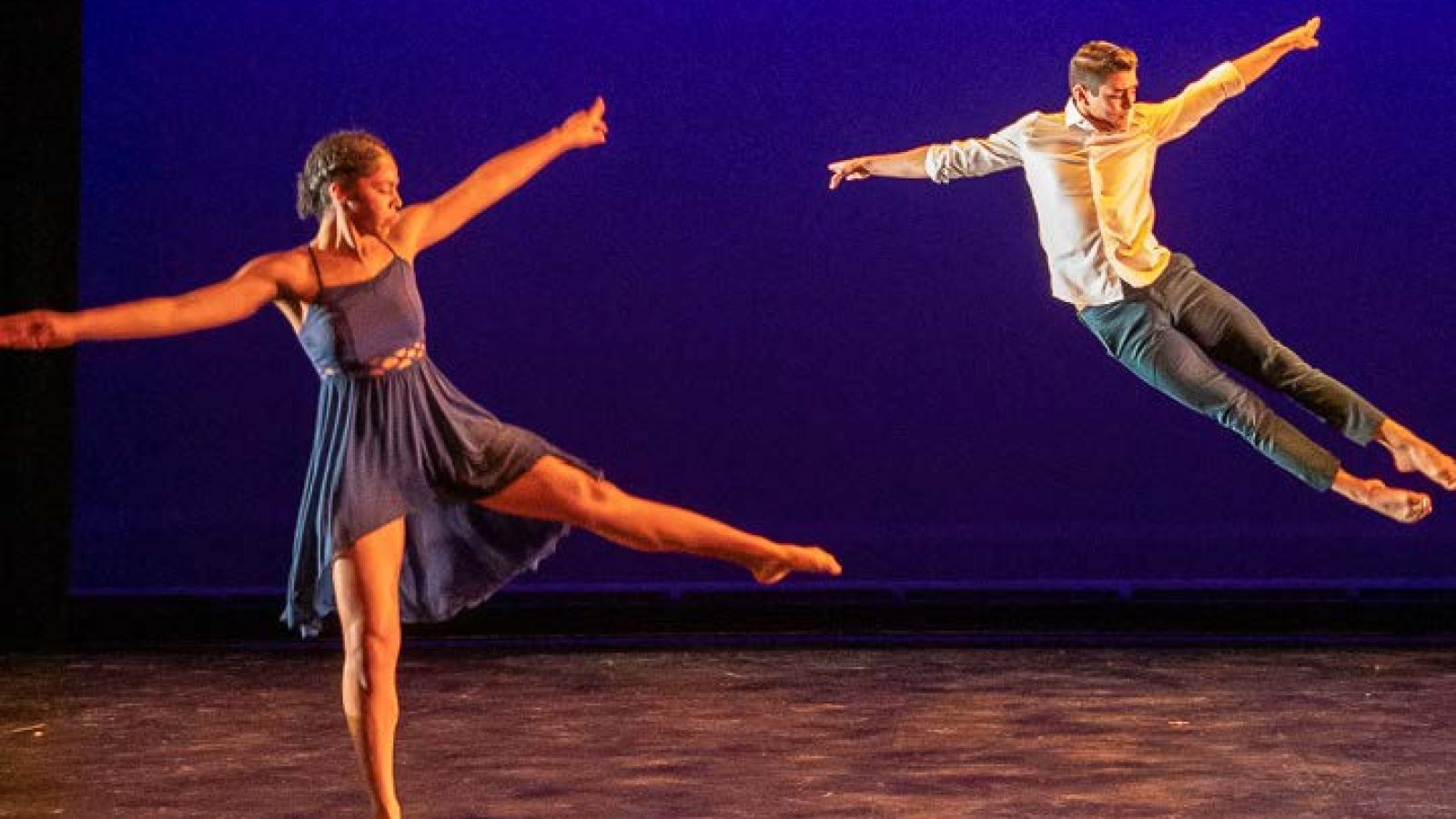 A duo of Black Movements Dance Theatre dancers leaps across the stage.