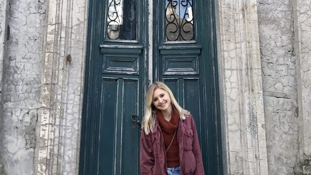 Grace Keegan stands in front of an old door on a stone building
