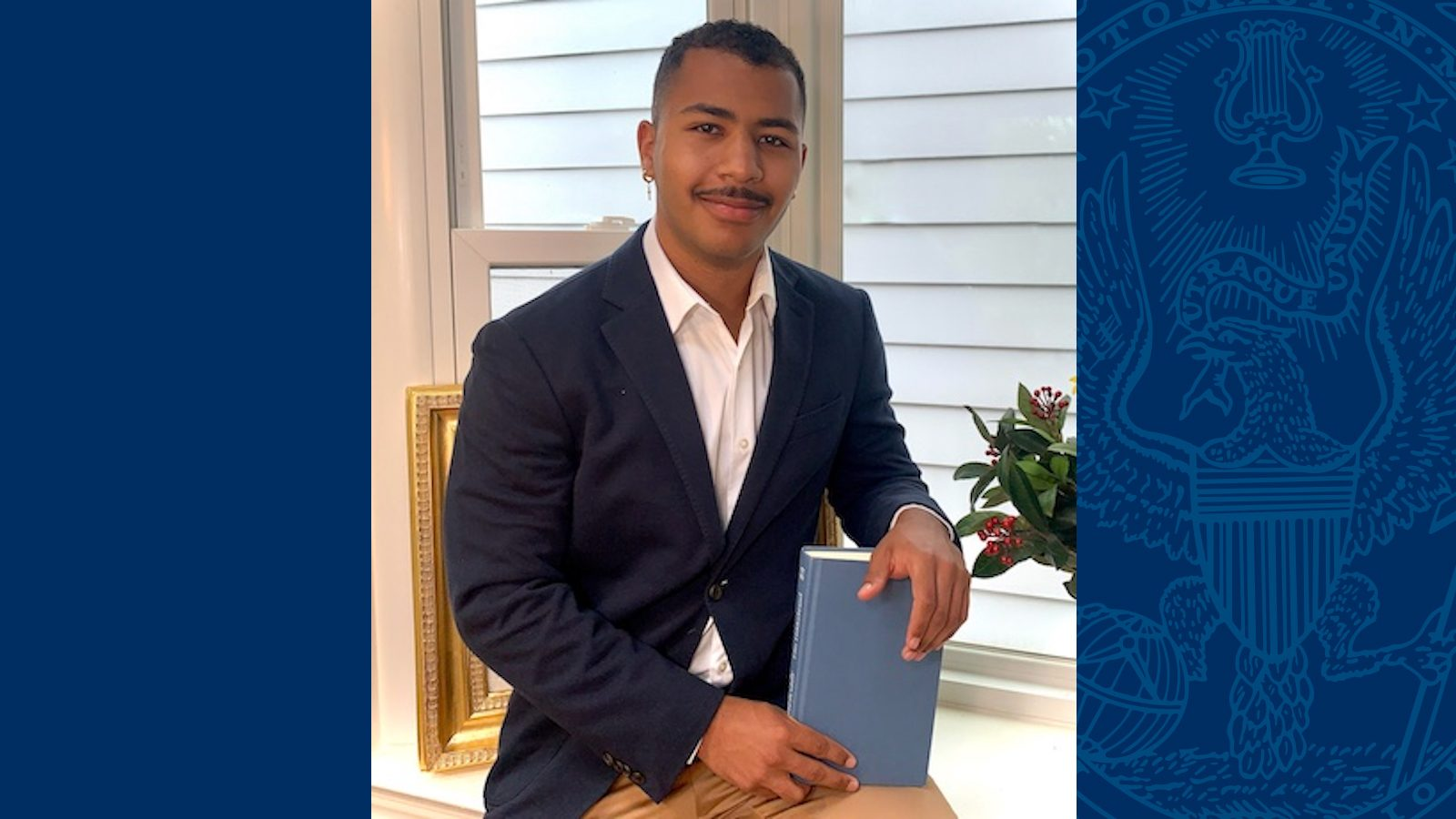 Isayah Henry wears a blazer and holds a book