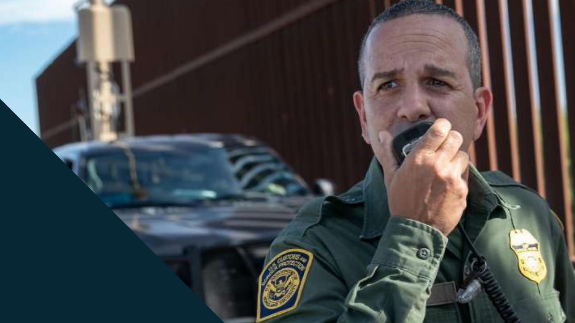 A Customs and Border Protection officer speaks into a radio in front of the wall at the US-Mexico border