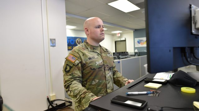Doug Meyer wears army uniform while standing in front of a computer