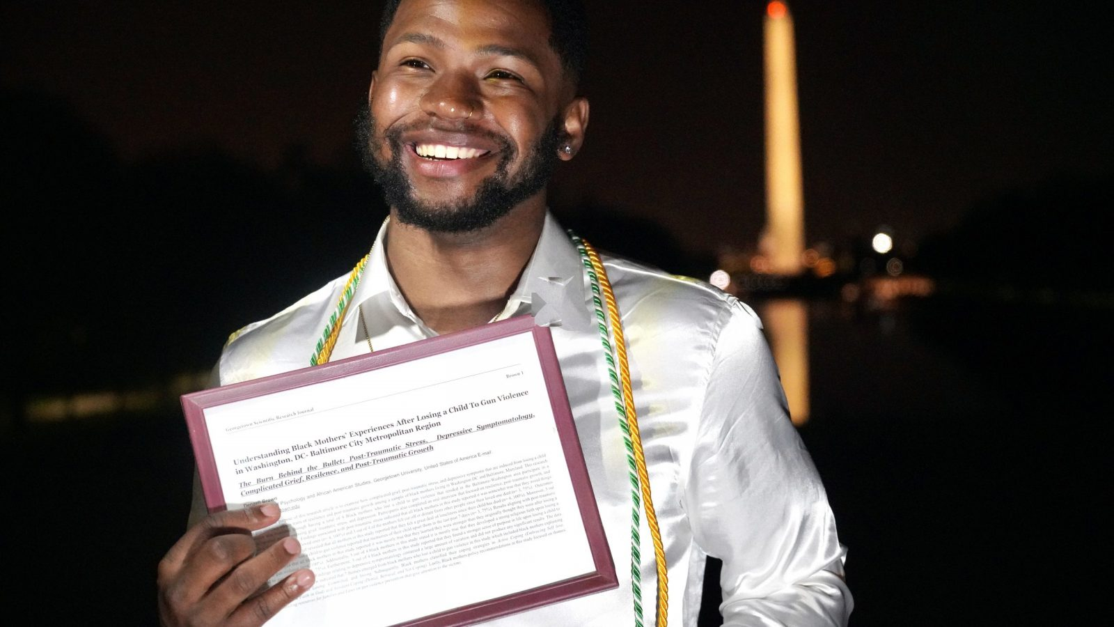 Denzell Brown holds his research in front of Washington Monument at night
