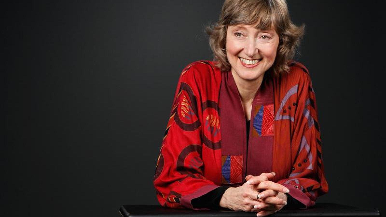 Deborah Tannen wears a red jacket in front of a black background