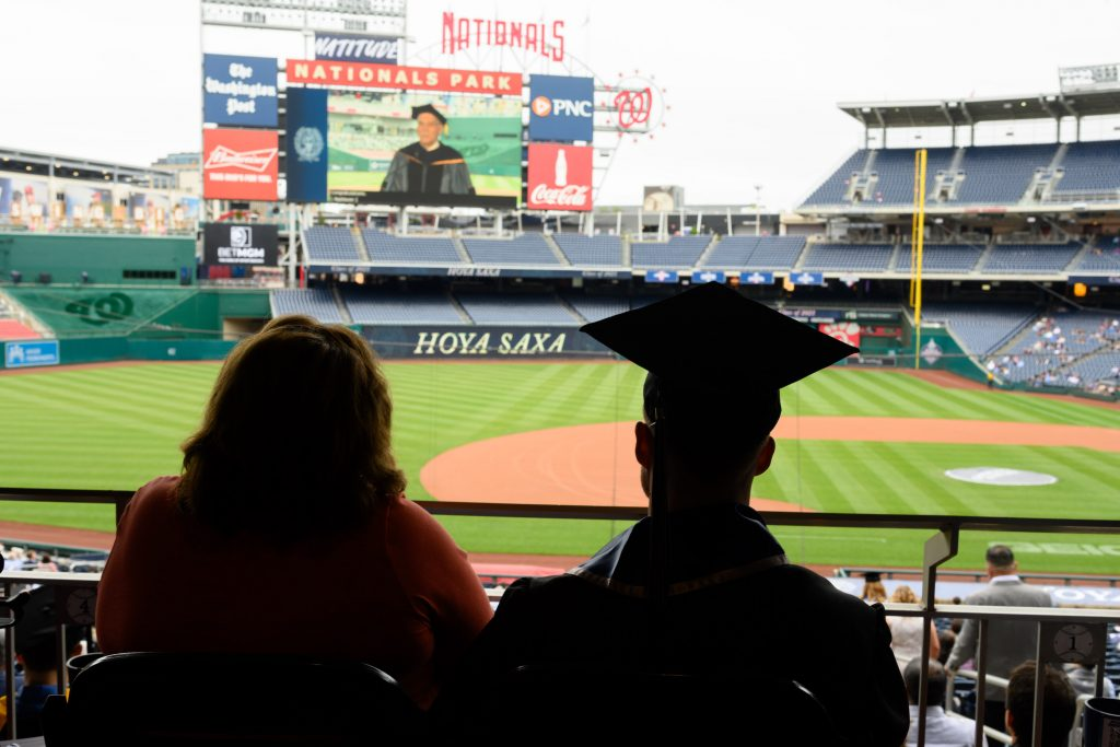A graduating student and their guest look at Nats Park