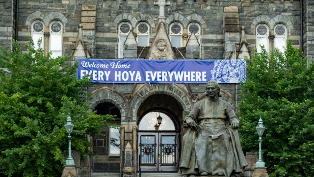 John Carroll statue in front of Healy Hall with the sign