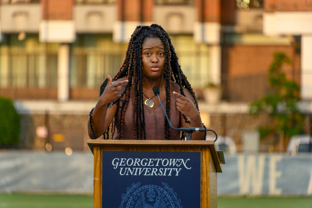 """Nile Blass speaks from a podium with a """"Georgetown University"""" sign"""